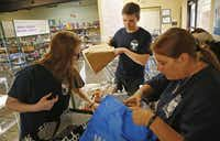 Anna Lawhorn (left), 16, Conner Brown (center), 16, and Lawhorn's mother, Wendy Auriemme, helps a client bag groceries in the food pantry at Allen Community Outreach in Allen.( Staff photo by ANDY JACOBSOHN  - DMN)