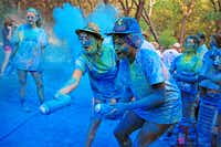 Parker Holt (left) and Rose Njoku, both 15, squirted walkers with colored powder during the Hanna 4 Hope 5K on Saturday in Rockwall.