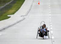 Addis Gonte, 20, hand cycles in his neighborhood in Sachse on July 17, 2013. At age 16, Gonte was in a car accident and suffered a spinal cord injury and traumatic brain injury. He has built himself up through doing weights, hand cycling and swimming.