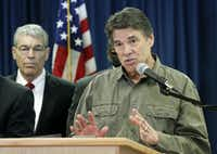 Texas Gov. Rick Perry answers questions from the media during a press conference at Texas Department of Public Safety headquarters Thursday in Austin.Vernon Bryant - Staff Photographer