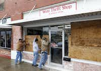 Charlie Yarborough, Pete Galvan, and Jay McNeil work on boarding up the West Thrift Shop in downtown West near the fertilizer plant explosion.(Vernon Bryant - Staff Photographer)