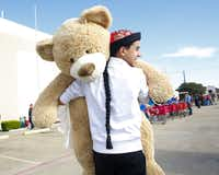Eyad Alrabbat carried an oversized teddy bear to the toy donation collection room for the MotorCops for Kids Toy Run at the Hella Shrine temple in Garland.
