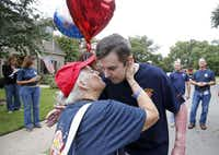 "Family friend Joyce Laux of Plano plants a big smooch on Jeff Patterson in front of his house. She was one of a crowd of well-wishers celebrating his return home. ""The generosity of people and the kindness of people. I've never felt alone,"" said Tina Patterson, his wife.( Vernon Bryant  -  Staff Photographer )"
