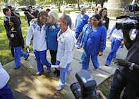 Texas Health Presbyterian nurse Chantea Irving got a kiss from senior vice president and chief nursing executive Joan Clark as they walked with chief nursing officer Cole Edmonson to the hospital after a news conference Monday.Vernon Bryant - Staff Photographer