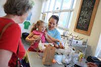 Kelcie Koerner holds her daughter Elizabeth, 5, as she picks out a pastry at Urban Acres.