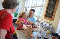 Kelcie Koerner holds her daughter Elizabeth, 5, as she picks out a pastry at Urban Acres.