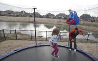 Gavin Woodward, 8 and Riley Woodward, 5, play on the trampoline in the backyard in Frisco on Wednesday, January 20, 2016. The backyard faces a six-acre open space that slopes down from their fence to a pond. The problem continues to escalate while the HOA and developer argue over who's responsible.(Vernon Bryant - Staff Photographer)