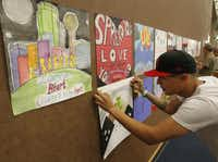 Volunteer Eduardo Morales of Dallas installs art pieces as part of the Dallas LOVE project at the J. Erik Jonsson Central Library.
