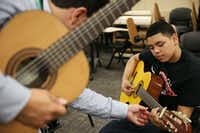 Camp instructor Adolfo Estrada (left) offers help to Daniel Nava (right), 16, of Irving, Texas, during a session he leads at the University of North Texas Mariachi Aguilitas Summer Camp.(Andy Jacobsohn - Staff Photographer)
