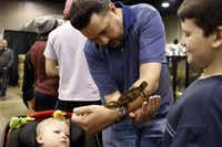From left: Aiden, Daniel and Ian Shoemake had a close encounter with a chameleon at the North American Reptile Breeders Conference and Trade Show in Arlington.