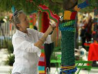 Volunteers including Lisa Payne wrapped park surfaces in knitted and crocheted decorations they've been producing for months.