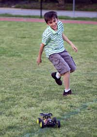 Diego Valle, 11, runs after a radio controlled off-road vehicle while his younger sister controls it in a Highland Park middle school field, Monday, April 28, 2014 in Dallas.Ben Torres  -  Special Contributor