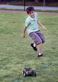 Diego Valle, 11, runs after a radio controlled off-road vehicle while his younger sister controls it in a Highland Park middle school field, Monday, April 28, 2014 in Dallas.( Ben Torres  -  Special Contributor )