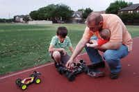 Diego and José inspect a radio-controlled vehicle that was slightly damaged during maneuvers on the grounds of McCulloch Intermediate School.( Ben Torres  -  Special Contributor )