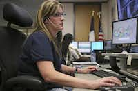 "Call taker Gina Liebert of Richardson listens to a 911 caller from the dispatch center in Plano Municipal Center. Plano's new system categorizes calls, based on a protocol of questions from 911 call takers, into ""priority one"" or ""priority two.""( Andy Jacobsohn  -  Staff Photographer )"