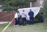 Frisco fire and police officials covered the back gate as they investigated at a home where a body was found in the pool and another inside on Wednesday.( Vernon Bryant  -  Staff Photographer )