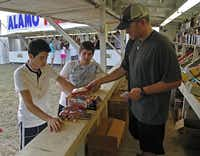 Plano residents Erick Martinez (left), 17, and Adam Jimenez, 16, are helped by Jonathan Thiebaud (right) of Stanton at the Alamo Fireworks stand on Parker Rd. in Allen on Tuesday, July 1, 2014. (Stewart F. House/Special Contributor)( Stewart F. House  -  Special Contributor )