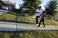 John Thomas Jr., 12, and his sister Camile Thomas, 7, walk through their neighborhood -- one of the areas targeted for major renovation through Habitat for Humanity's Dream Dallas initiative.