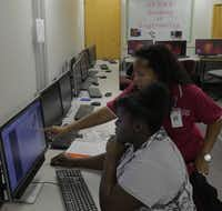 Kimball High School student Tayunna Penny, 16 (seated), works with Giardina on a computer project in the Introduction to Engineering and Design class.( Staff photo by Ron Baselice  -  DMN )