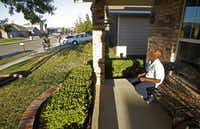 John Thomas Jr., 12, sits on the front porch of his house in one of the neighborhoods targeted for renovation in a Habitat for Humanity program.