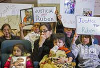 Martha Anjelica Romero, holding Abdiel, 1, and flanked by her children Keila García (left), 4, and Edwin Romero, 10, sits on the front row. Her unarmed husband, Rubén García Villalpando, 31, was shot to death by a Grapevine officer.(Ashley Landis - Staff Photographer)