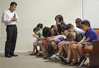 Children's minister Cholo Khongrath leads a prayer for youths sitting in the front pew during a bilingual Sunday service at First Laotian Baptist Church.(Tom Fox - Staff Photographer)