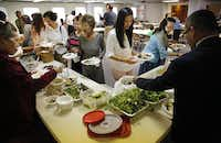 "Laotian Baptist parishioners share homemade dishes after the service. ""When you eat something it takes you back, that takes you to your core roots,"" said one churchgoer.(Tom Fox - Staff Photographer)"