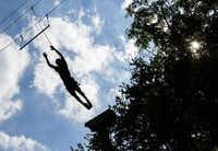 """Eduardo Nery, 18, jumps from the top of a pole to a bar hung by wires at Camp I-Thonka-Chi near Meridian. It is tradition for graduating campers to take the leap on the last day of camp, where activities are designed to challenge the kids physically and emotionally. The camp's director, Donna Crump, Parkland's physical therapy manager, said adapting to a burn injury doesn't end when a patient is released from the hospital. """"The trauma, the stares, that happens when they're back home,"""" she said.( Ashley Landis  - Staff Photographer)"""
