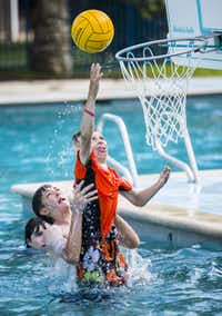 Clay Fite,  11, gets some help from Billy Clay, 13, while playing water basketball. Camp director Crump said the activities help campers meet and befriend other burn survivors their age because no one stares at their scars.( Ashley Landis  -  Staff Photographer )
