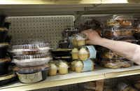 Volunteer Kathy Draxler picks a pack of cupcakes as she prepares food for a client.
