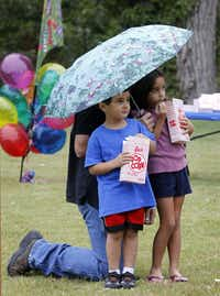 Rick Peters holds an umbrella for his son, Luke Peters, 4, and daughter Alexa Peters, 6, during an  Oct. 5 ribbon-cutting celebrating the completion of a $2.1 million project to renovate and update the elaboroate stonework built in the 1930s by Works Progress Administration crews at Reverchon Park in Dallas.Michael Ainsworth - Staff Photographer