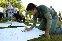 Rodolfo Guel works on a protest sign at Oak Cliff Founders Park before the start of the We Are Not Trash march on Saturday.