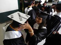 West High graduate Andy Ward has his hat adjusted by classmate Karen Tamayo. His hat memorializes the April fertilizer plant explosion. Ward was a dietitian's assistant at West Rest Haven nursing home at the time of the explosion and carried many of the injured residents to the football field that night.