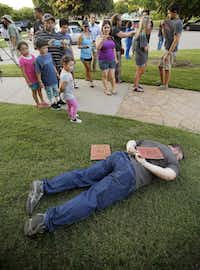"A silent protester lay in the grass Monday in a pose similar to that of the girl who was pinned by a police officer Friday. The protester's signs read, ""We Stand United"" and ""Justice For All.""(Tom Fox - Staff Photographer)"