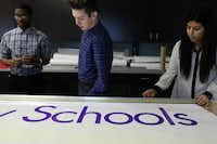 Dubiski Career High School students (from left) Rayford Starr II, 15, Stephen Bronder, 16, and Yolanda Alvarado, 14,  prepare a sign for the GPISD Experience Open House on Saturday.