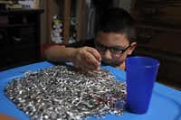 Gabriel Antonio Pedroza, 10, helps sort soda can tabs for his mother's creations at their home in Denton on Monday, June 9, 2014. Maria Luisa Pedroza makes belts, purses, bracelets and other items from from soda can tabs and puts some of the money from the sales into her children's bank accounts.( Lara Solt  -  Staff Photographer )
