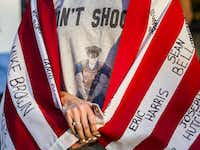 Mallory Rouse wore an American flag Tuesday with names of people many say are victims of police brutality. She was part of the protest at Arlington police headquarters.( Ashley Landis  -  Staff Photographer )