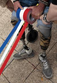 Disabled Army veteran Stephen Garner of Garland helped put down red, white and blue tape as part of Project Freedom Road on Sunday at Dallas City Hall.  They striped the route for Monday's Veterans Day parade.