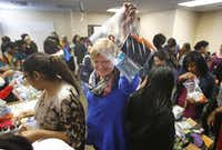"""Stephanie Cole passes along a gift bag as volunteers make them for clients at Genesis Women's Shelter on """"Be A Blessing Day"""" at the Meadows Building in Dallas.(Louis DeLuca - Staff Photographer)"""