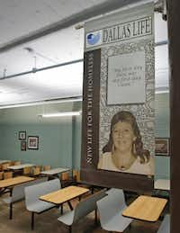 A banner in the lunch room celebrates the success of former client Brigitte DeHart, who now works at Dallas Life.( Staff photo by LOUIS DELUCA  -  DMN )