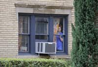 A resident peeks out the window at an apartment next door to the residence at 5700 block of  Marquita, where reportedly a person diagnosed with Ebola lived, photographed in Dallas on Sunday, October 12, 2014.  (Louis DeLuca/The Dallas Morning News)Louis DeLuca - Staff Photographer