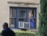 A resident peeks out the window at an apartment next door to the residence at 5700 block of  Marquita, where reportedly a person diagnosed with Ebola lived, photographed in Dallas on Sunday, October 12, 2014.  (Louis DeLuca/The Dallas Morning News)(Louis DeLuca - Staff Photographer)