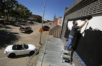 Painter and tattoo artist Lucas Cervellini paints the marquee on the new Intrinsic Smokehouse & Brewery storefront on the downtown Garland square. Owner Cary Hodson and his brother-in-law Casey Vincent (business partner) are renovating a 1910 building for a barbecue restaurant and brewery opening in December.( Staff photo by TOM FOX  -  DMN )