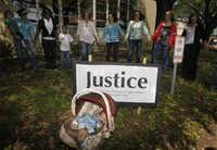 Angel Diaz, 3 months, daughter of Lorena Martinez, not pictured,  rests as other pray during a prayer walk around the Kaufman County Courthouse in Kaufman, Texas on April 14, 2013.  (Michael Ainsworth/The Dallas Morning News)(Michael Ainsworth - Staff Photographer)