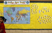 A world map displays photos of students and their country of origin in a main hallway at Wallace Elementary.