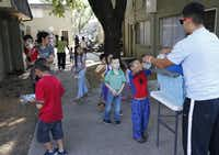 AmeriCorps volunteer Gilbert Castillo handed out breakfast meals to children at the El Sol del Lago apartments in Dallas on Tuesday. The CitySquare summer program dishes out games and activities for kids along with food.( David Woo  - Staff Photographer)
