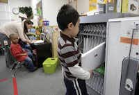 Jason Luu, 5, returns a laptop to the COW (computer on wheels) cart at Beaver Elementary in Garland.