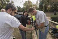 Doug Greene (left) Sally Huang and Bob Osborne, along with other volunteers with the Texas Ramp Project, build a wheelchair ramp for a disabled man in a South Dallas neighborhood. The Richardson-based organization has built over 10,000 ramps all over the state.( Rex C. Curry  -  Special Contributor )