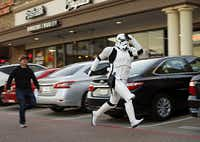Taylor Wren, dressed as a Stormtrooper, raced across a strip shopping center parking lot as he was running late to a group photo outside the Alamo Drafthouse cinema in Richardson, where Star Wars: The Force Awakens movie was showing Dec. 17, 2015. He was hurried along by friend David Petty. (Tom Fox/The Dallas Morning News)