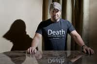 """Michael Nealon poses in his """"Death: Been there. Done that. Got the T-shirt"""" shirt in his Lake Dallas home. Nealon says he was technically dead for seven minutes during his 2009 accident, before rescuers performed CPR."""